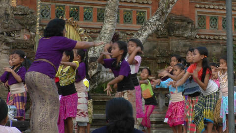 A woman leads a group of girls in dance movements at an Indonesian ceremony Footage