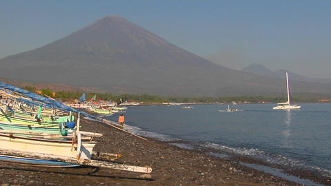 Small waves lap at a shore lined with boats in Indonesia Stock Video Footage