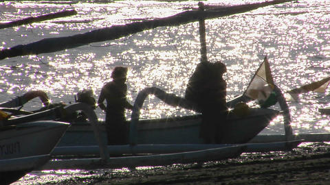 people work on a boat near the shimmering ocean Stock Video Footage