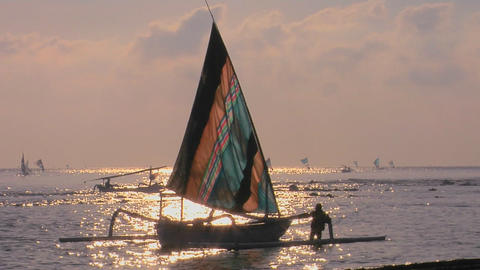 A man guides a sailboat to shore Stock Video Footage