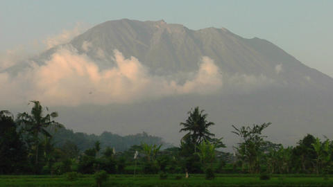 Clouds move slowly in front of a tall mountain range Stock Video Footage