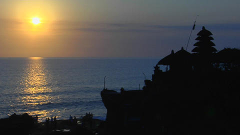 The sun shines over the water near the Pura Tanah Lot... Stock Video Footage