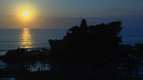 The Pura Tanah Lot temple in Bali, Indonesia is silhouetted against the water Footage