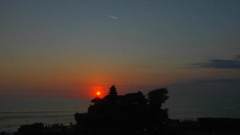 The sun hangs low in the sky near the Pura Tanah Lot... Stock Video Footage