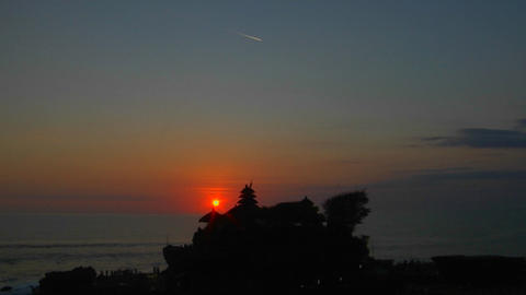 The sun hangs low in the sky near the Pura Tanah Lot temple in Bali, Indonesia Footage
