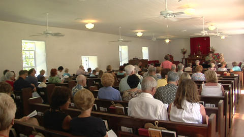 The interior of a small town church with many worshippers Footage