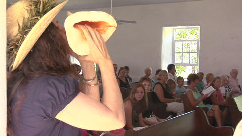 A woman blows a conch shell during a church service in Hawaii Footage
