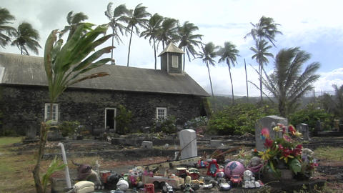 Wind blows over a heavily decorated grave on a tropical island Footage