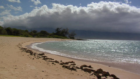 Waves roll into a white sand beach in Hawaii Footage