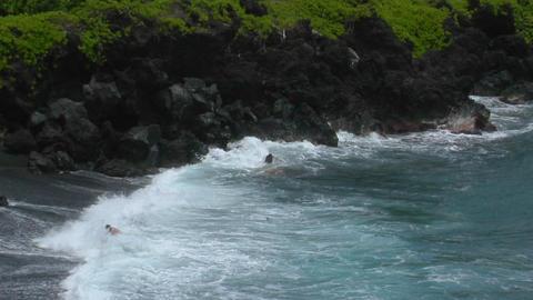 A man battles a large ocean swell on a black sand beach... Stock Video Footage