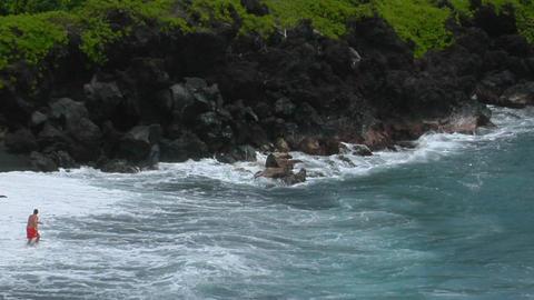 A man battles a large ocean swell on a black sand beach in Hawaii Footage