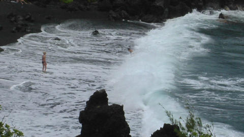 A man battles large waves along a black sand beach in Hawaii Stock Video Footage