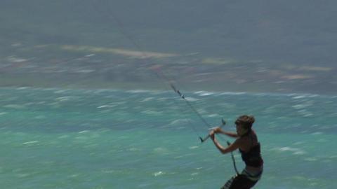 Windsurfers glide across a sparkling ocean Stock Video Footage