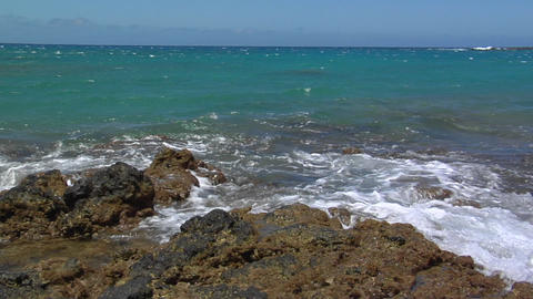 Pan across ocean waves lapping against volcanic shore Stock Video Footage