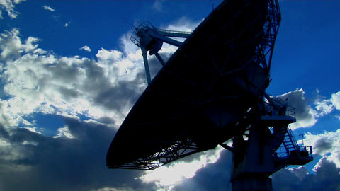 A satellite dish is silhouetted against the sky Stock Video Footage