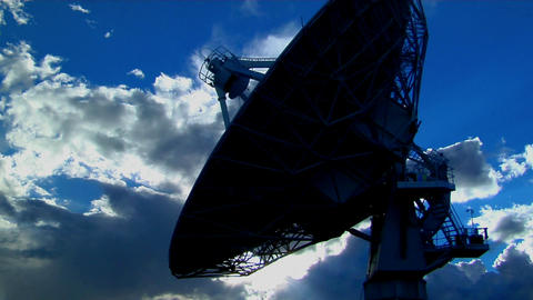 A satellite dish is silhouetted against the sky Footage