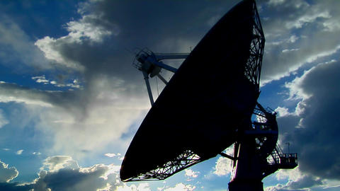A satellite dish moves in time lapse and is silhouetted... Stock Video Footage