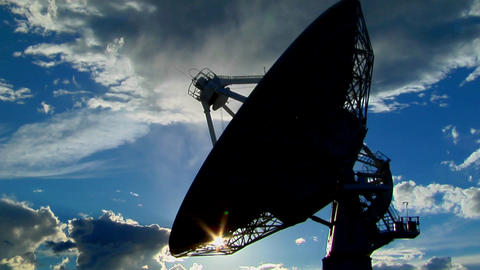 A satellite dish moves in time lapse and is silhouetted against the sky Footage