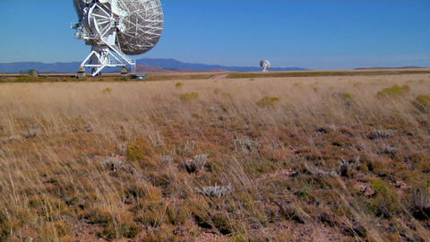 A tilt up from a windswept field to distant satellite dishes Stock Video Footage