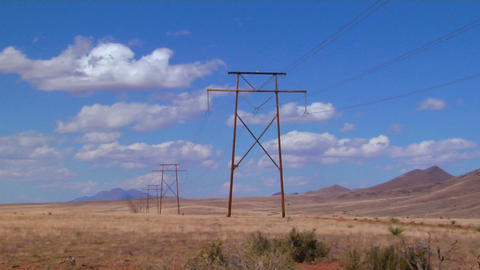 Time lapse of clouds moving behind power lines Stock Video Footage