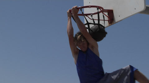 A basketball player slam dunks while standing on a step... Stock Video Footage