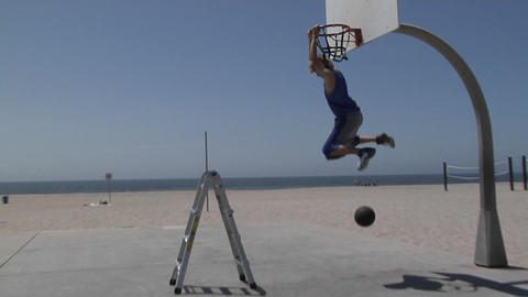 A basketball player slam dunks while standing on a step ladder Live Action