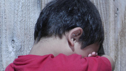 A young boy hides his face in arms Stock Video Footage