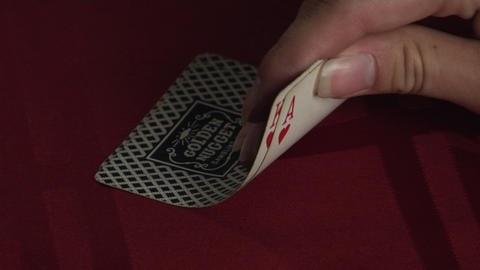 A hand turns up the corner of two playing cards to reveal a King and an Ace Footage