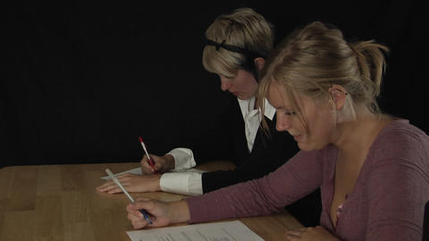 women sit at a table and fill out paperwork Stock Video Footage