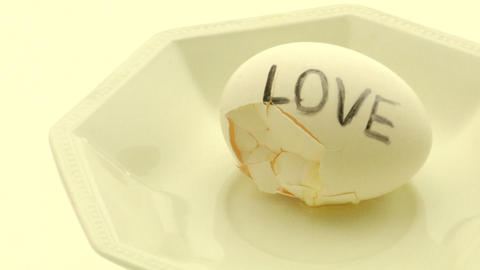 "A woman's hand picks up a hardboiled egg with the word Love"" written on it and cracks it Footage"