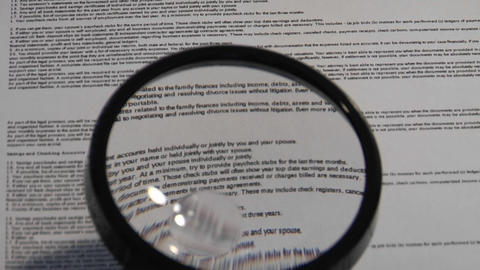 A magnifying glass passes over a paper to reveal the... Stock Video Footage