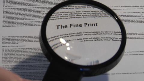 A magnifying glass passes over a paper to reveal the words The Fine Print Footage