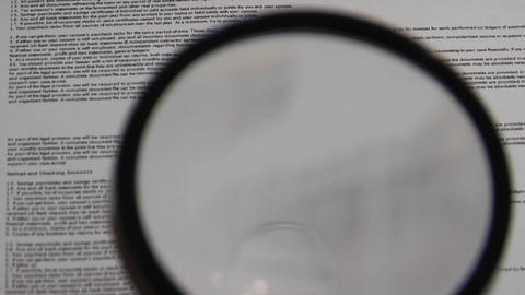 Magnifying glass passes over paper to reveal the words... Stock Video Footage