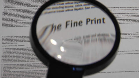 Magnifying glass passes over paper to reveal the words The Fine Print Footage