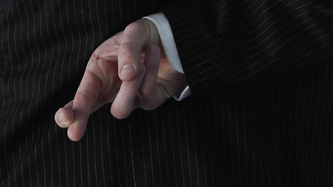 A businessman crosses his fingers behind his back Footage