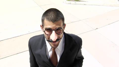 A businessman smokes a cigar wearing a Groucho Marx style face mask Footage