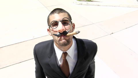A businessman smokes a cigar wearing a Groucho Marx style... Stock Video Footage