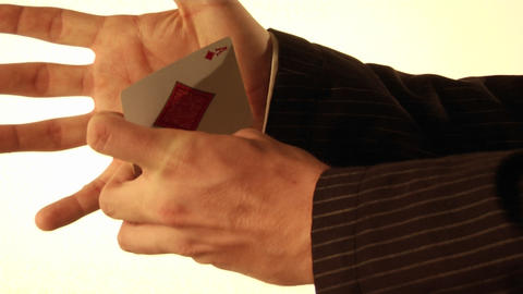 A man tucks a playing card into his shirt sleeve Footage