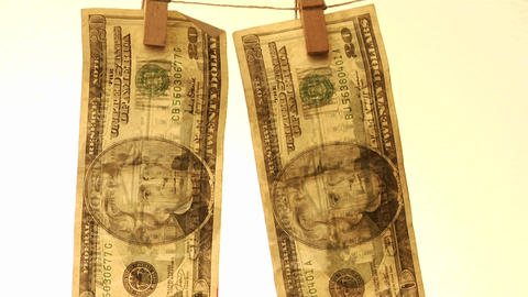 20 dollar bills hang from a clothesline clipped with clothespins Footage