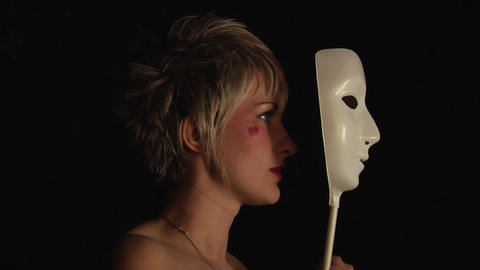 A woman with a heart painted on her cheek holds a white mask up to her face Footage