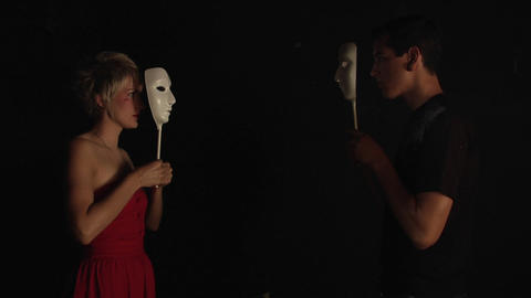A couple faces each other and covers their faces with white masks Footage