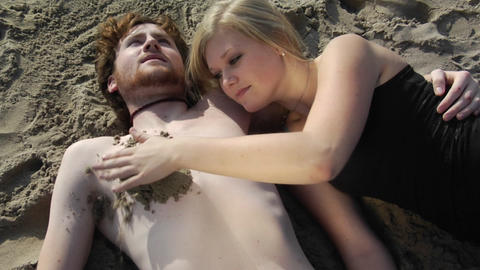 A woman packs sand on a mans bare chest, then draws a heart in it with her finger, while they lay on Footage