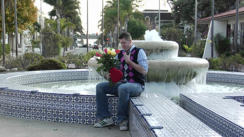 A man waits excitedly at a fountain with flowers and a... Stock Video Footage