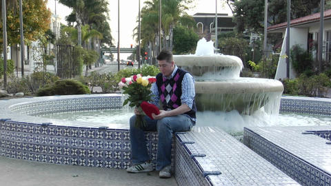 A man waits excitedly at a fountain with flowers and a heart-shaped box Footage