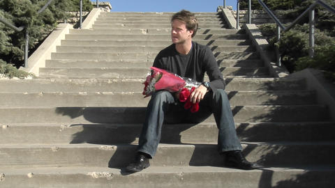 A man waits on the stairs with flowers and a teddy bear Footage