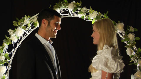 Bride and groom stand under an arch of flowers as the man... Stock Video Footage