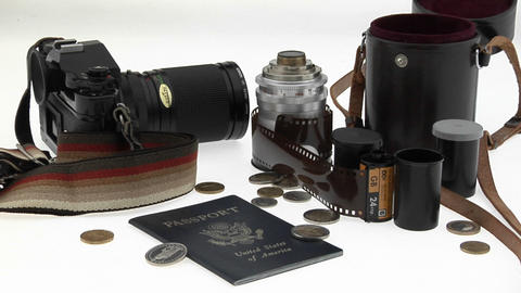 A passport, coins, camera and equipment sit on a white table Stock Video Footage
