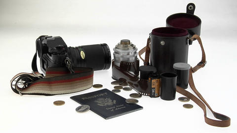 A passport, coins, camera and equipment sit on a white table Footage