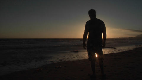 A man stands alone on a windy beach Stock Video Footage