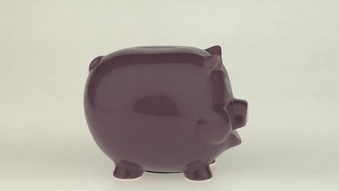 A woman's hand puts a coin into a pink piggy bank Stock Video Footage